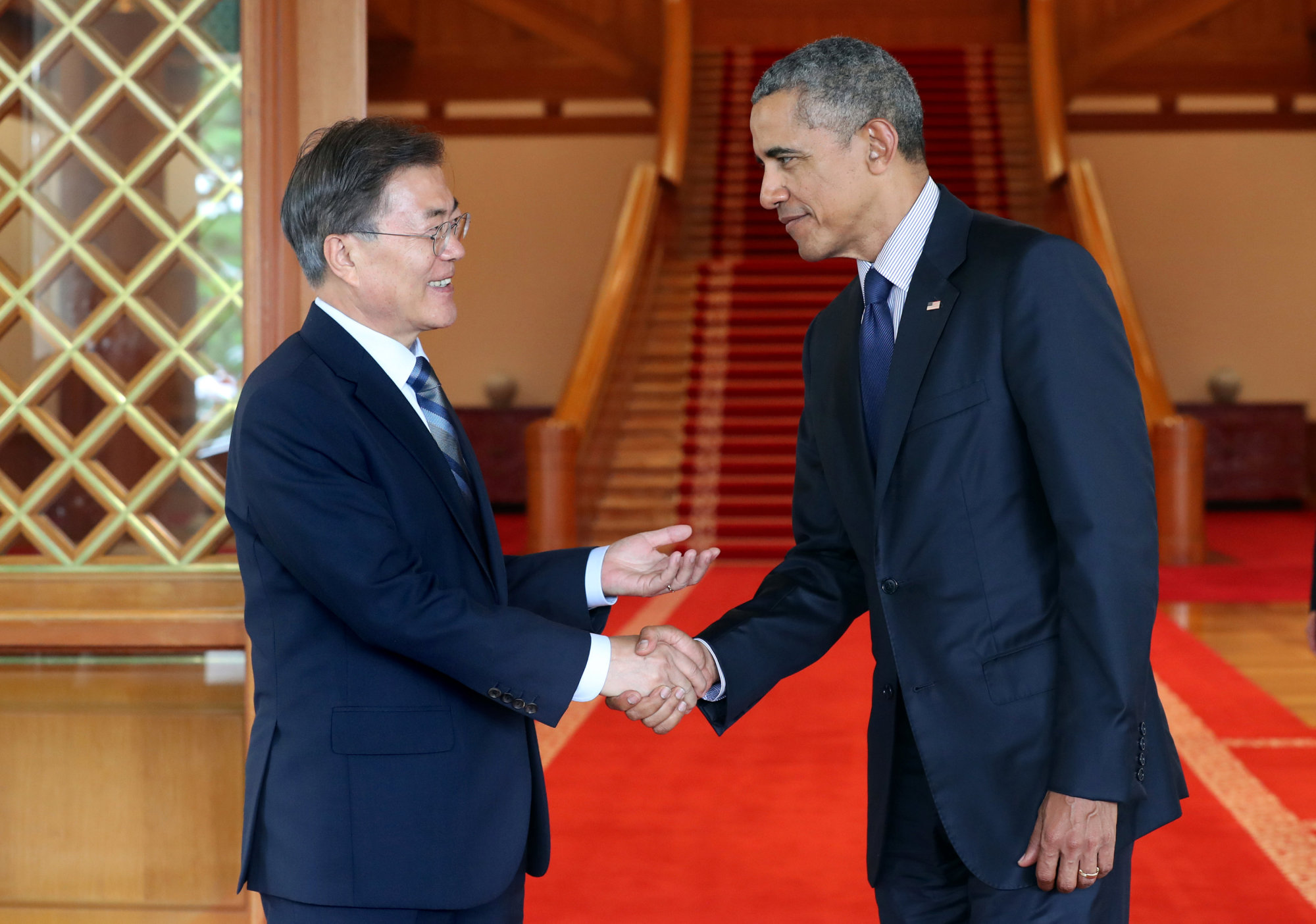 South Korean President Moon Jae-in shakes hands with former U.S. President Barack Obama at the Presidential Blue House in Seoul on Monday.   REUTERS
