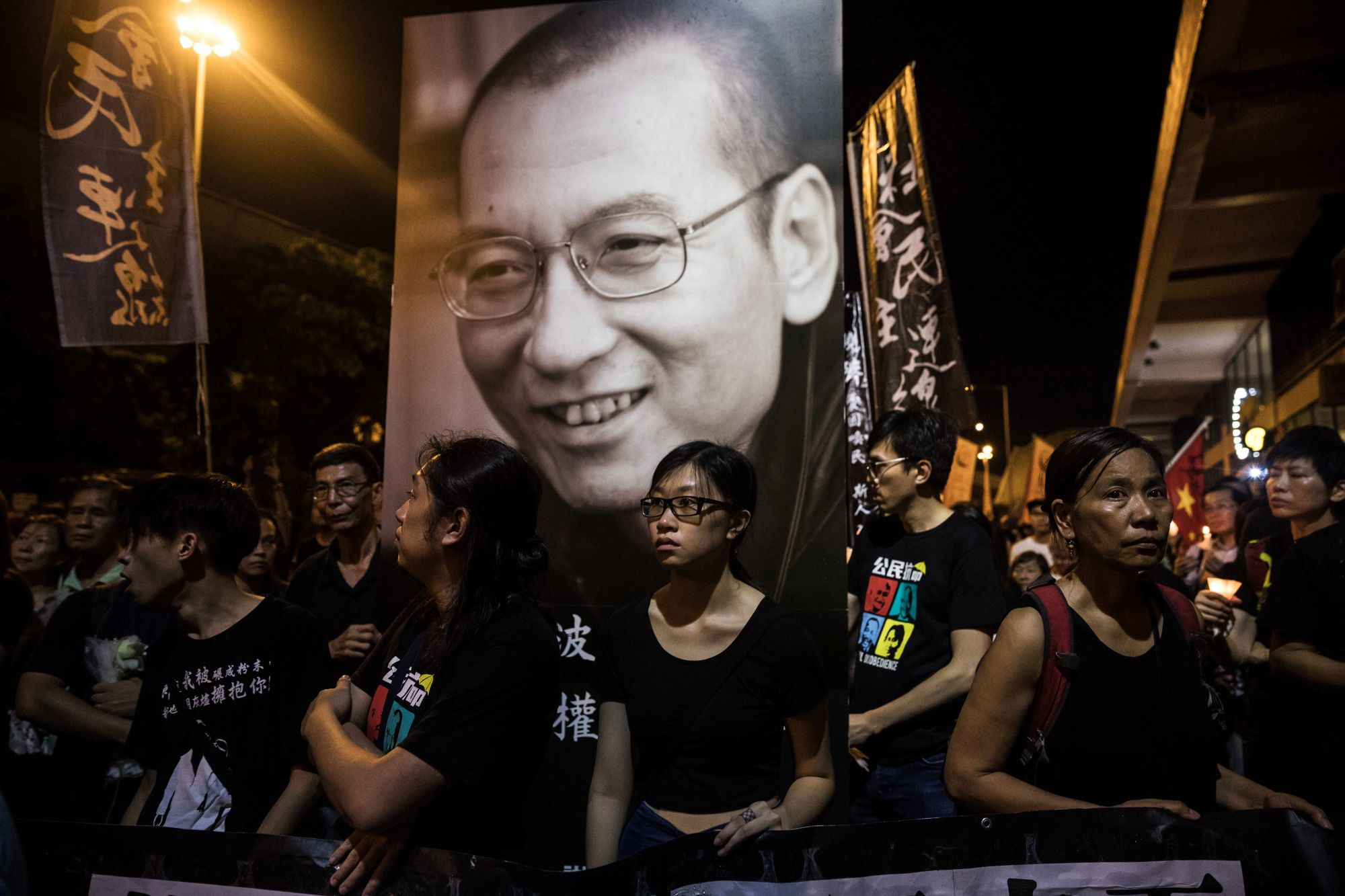 People attend a march for the late Chinese Nobel laureate Liu Xiaobo in Hong Kong on Saturday. | AFP-JIJI