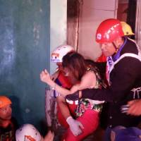 Rescuers carry a rescued resident from the rubble of a destroyed building after a 6.5 magnitude earthquake hit the town of Kananga, Leyte province in central Philippines, on Thursday. | AFP-JIJI