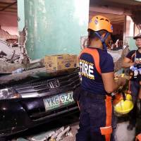 Rescuers stand next to a car buried under the rubble of a destroyed building on Friday after a 6.5 magnitude earthquake hit the town of Kananga in the Philipines' Leyte province. | AFP-JIJI