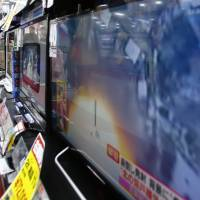 Children watch TV news shows reporting on North Korea's satellite launch at an electronics store in Tokyo in February 2016. | AP