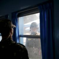North (right) and South Korean soldiers look at each other through a window of a conference room in the United Nations Command Military Armistice Commission Conference Building at the truce village of Panmunjom, South Korea, in 2016. | REUTERS