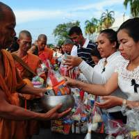 Buddhist monks wait receive alms from well-wishers during the birthday celebrations for Thai King Maha Vajiralongkorn in the southern Thai province of Narathiwat on Friday. | AFP-JIJI