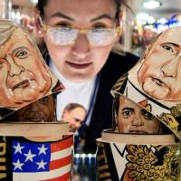 A woman looks at traditional Russian wooden nesting Matryoshka dolls depicting U.S. President Donald Trump (L) and Russian President Vladimir Putin at a gift shop in central Moscow Thursday. Trump is due to meet his Russian counterpart Putin on Friday during the G-20 summit in Germany.   AFP-JIJI