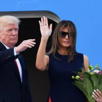 U.S. President Donald Trump and first lady Melania Trump wave after stepping on Air Force One prior their departure from Chopin Airport in Warsaw to Hamburg, Germany, Thursday.   AFP-JIJI