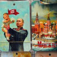 A drawing of Russian President Vladimir Putin holding a baby with the face of U.S. President Donald Trump, based upon a propaganda poster showing late Soviet leader Joseph Stalin holding a baby, is displayed at a souvenir kiosk in Moscow on Wednesday. | AFP-JIJI