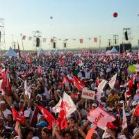 People cheer as Turkey's main opposition Republican People's Party (CHP) leader Kemal Kilicdaroglu throws flowers to supporters during a rally on Sunday in Istanbul marking the end of his 450-km 'justice march' from Ankara to Istanbul. | AFP-JIJI