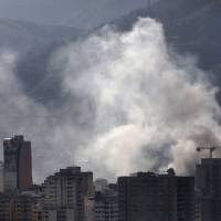 Smoke rises from a police station that was set on fire while the Constituent Assembly election was being carried out in Caracas Sunday. | REUTERS