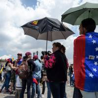 Venezuelans residing in Colombia take part in a symbolic plebiscite called by the Venezuelan opposition on President Nicolas Maduro's project of a future constituent assembly, in Bogota, on Sunday. | AFP-JIJI