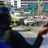An anti-government activist clashes with security forces during a protest over the elections for a Constituent Assembly proposed by Venezuelan President Nicolas Maduro in Caracas on Sunday. | AFP-JIJI