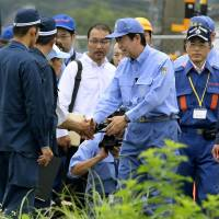 Prime Minister Shinzo Abe greets a resident of Hita, Oita Prefecture, on Wednesday during his visit to the disaster-stricken city. | KYODO