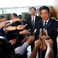 Shinzo Abe speaks to reporters as he arrives at the Prime Minister's Office on Monday in the wake of his Liberal Democratic Party's crushing defeat in the Tokyo Metropolitan Assembly election. | REUTERS