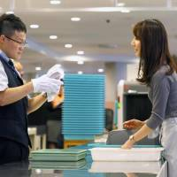 An airport security worker checks a passenger's luggage during a training session last month at Narita airport. | KYODO