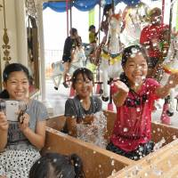 Children play while riding a merry-go-round featuring bathtubs instead of seats at a temporary amusement park in Beppu, Oita Prefecture, on Saturday. | KYODO