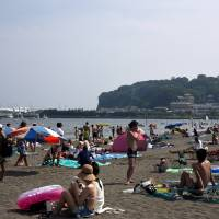 Sun spot: Visitors enjoy Katase Beach, which sits across from Enoshima island (right).