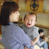A mother holds her crying baby in Tokyo in June. | KYODO