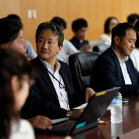 Motoyuki Yufu (center), deputy director-general of the Planning and Coordination Bureau at the Financial Services Agency, holds a meeting with other FSA staff, investors and influential bloggers at the agency in Tokyo on June 29. | REUTERS