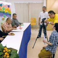 Members of Pansy Media, including many who are intellectually disabled, shoot an online program on June 15 in Higashiosaka, Osaka Prefecture. | COURTESY OF MIKI / VIA KYODO