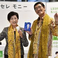 Tokyo Gov. Yuriko Koike and comedian Pikotaro hold energy-efficient LED lightbulbs at a Tokyo Metropolitan Government event Monday to promote a free exchange program aimed at accelerating the replacement of incandescent lights. | KYODO