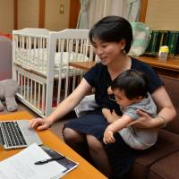 Local lawmaker Misaki Hibi works while caring for her son in a day care room set up inside Nagoya City Hall by Democratic Party members of the municipal assembly. | CHUNICHI SHIMBUN