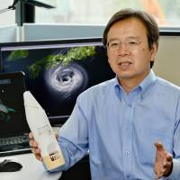 Nagoya University professor Kazuhisa Tsuboki explains his team's project to analyze supertyphoons, holding an expendable device for collecting data on temperatures, air pressure and wind speeds in typhoons. | CHUNICHI SHIMBUN
