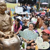 Protesters gather next to a statue symbolizing the 'comfort women' in front of the Japanese Embassy in Seoul on Wednesday. | KYODO