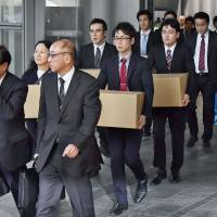Tokyo Labor Bureau officials leave the headquarters of Dentsu Inc. in Tokyo in November 2016 after raiding the office in suspicion that the firm made its employees work illegally long hours. KYODO
