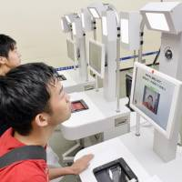 People try out immigration machines that use facial recognition during an experiment at Narita International Airport in 2014. | KYODO