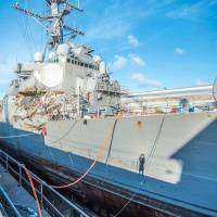 The USS Fitzgerald sits in Dry Dock 4 at Fleet Activities Yokosuka in Yokosuka, Kanagawa Prefecture, on July 11 for repairs and damage assessment after its fatal June 17 collision with a merchant vessel near Tokyo Bay.   REUTERS