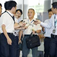 Gen. Toshiya Okabe is surrounded by reporters as he enters the Defense Ministry on Thursday. | KYODO