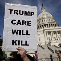 A demonstrator opposed to the Senate Republican health care bill marches near the U.S. Capitol in Washington last month. | BLOOMBERG