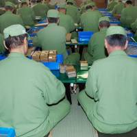 An undated photo shows inmates working at a prison. The Justice Ministry plans to offer translation services for non-Japanese inmates nationwide through video phones, starting in November.   KYODO