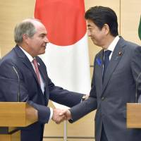 Prime Minister Shinzo Abe and Jordanian Prime Minister Hani al-Mulki shake hands after a news conference at the Prime Minister's Office in Tokyo on Friday. | KYODO