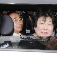 Yasunori Kagoike, the former chief of scandal-hit school operator Moritomo Gakuen, and his wife, Junko, are taken to the Osaka District Public Prosecutor's Office last Thursday. | KYODO