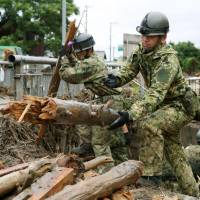 Members of the Self-Defense Forces search for missing people in Asakura, Fukuoka Prefecture, on Sunday. | KYODO