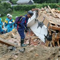 Rescuers work with a police dog near a damaged house in Asakura, Fukuoka Prefecture, on Tuesday as they search for the missing.   KYODO