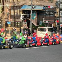 Tourists are seen driving rented MariCar go-karts in Minato Ward, Tokyo, in February. | MAGDALENA OSUMI