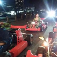 A couple in a group of four Australians snap photos at an intersection during a two-hour go-kart tour in Tokyo on June 17. | KYODO