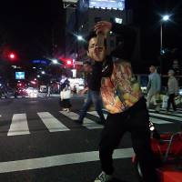 A tour guide and lead driver for go-kart operator EcoKart L.L.C., takes photos at an intersection in the Roppongi  district during a two-hour tour of Tokyo on June 17. | KYODO