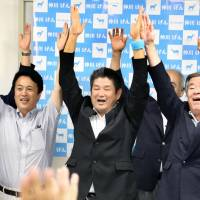 Nara Mayor Gen Nakagawa (center) and his supporters celebrate at his campaign office in the city early Monday after he won a third term. | KYODO