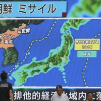 People walks past a public TV screen broadcasting news of North Korea's ballistic missile which landed in the waters of Japan's economic zone in Tokyo on Tuesday. | AP
