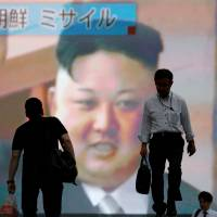 Men walk past a large television in Tokyo showing news of North Korea firing an intercontinental ballistic missile on July 4.   REUTERS