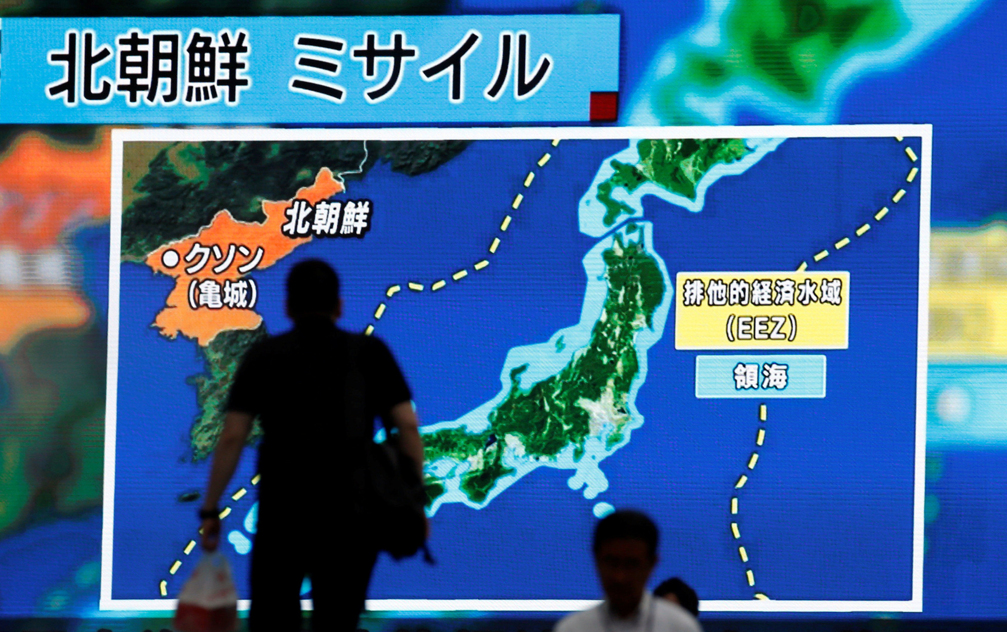 Passers-by in Tokyo on Tuesday look at a large monitor showing news of North Korea's intercontinental ballistic missile test. | REUTERS