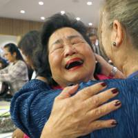 Setsuko Thurlow, who survived the atomic bombing of Hiroshima in August 1945, hugs a supporter after a landmark treaty banning nuclear weapons was adopted by the United Nations in New York on Friday. | KYODO