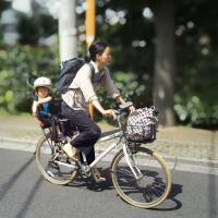 A woman takes her daughter to a day care facility in Tokyo earlier this month. | KYODO