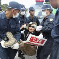 Riot police last month move a protester away from the gate of the U.S. Marine Corps' Camp Schwab in Nago, Okinawa Prefecture, adjacent to where construction of a new air base is underway.   KYODO