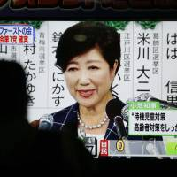 A pedestrian watches a big screen on a street in Tokyo July 2 as Tokyo Gov. Yuriko Koike's Tomin First no Kai (Tokyoites First) wins big in the Tokyo Metropolitan Assembly election earlier in the day. | KYODO