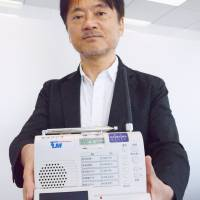 Tokyo Telemessage President Hidetoshi Seino, seen in Tokyo in May, holds a device that can receive pager frequencies. | KYODO