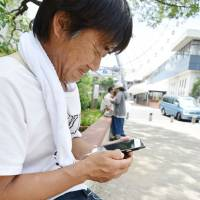 Tsutomu Misago, 48, plays 'Pokemon Go' during a visit to Tempozan Park in the city of Osaka earlier this month. | KYODO