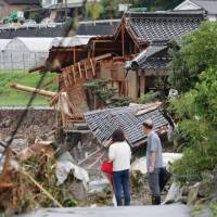 Houses in the city of Hita, Oita Prefecture, are destroyed on Thursday, following torrential rain which has fallen since Wednesday. While pledging to do its utmost to assist those hit by the storm, the government called on residents in the affected areas to protect themselves. | KYODO